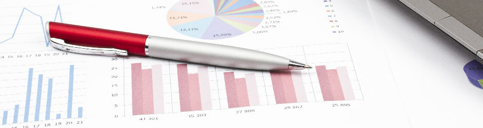 A pen laying on printed financial reports.