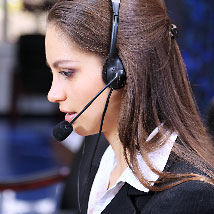Young woman talking on a phone headset.