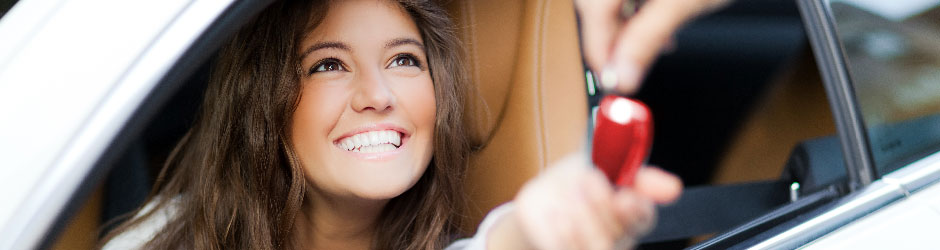 A teenage girl being handed car keys and smiling.